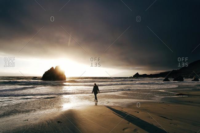 Woman walking on a seashore at sunset