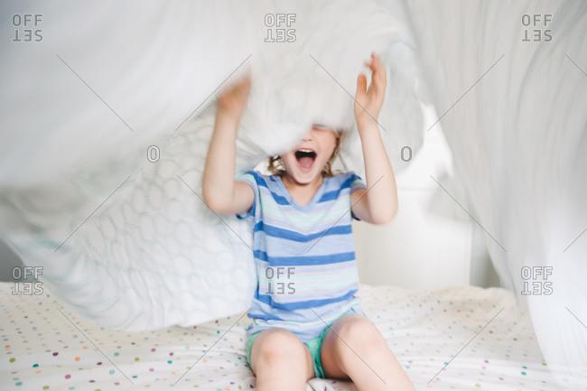 A girl yells underneath a sheet