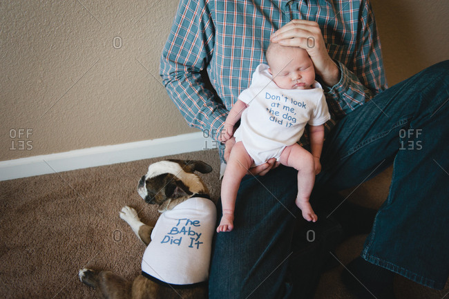 A man holds his newborn baby while siting next to his dog