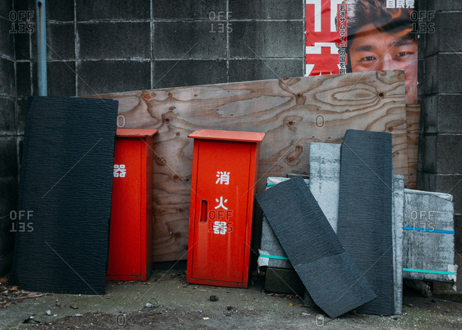 Zushi, Japan - January 14, 2015: Boards and trash leaning against advertisement