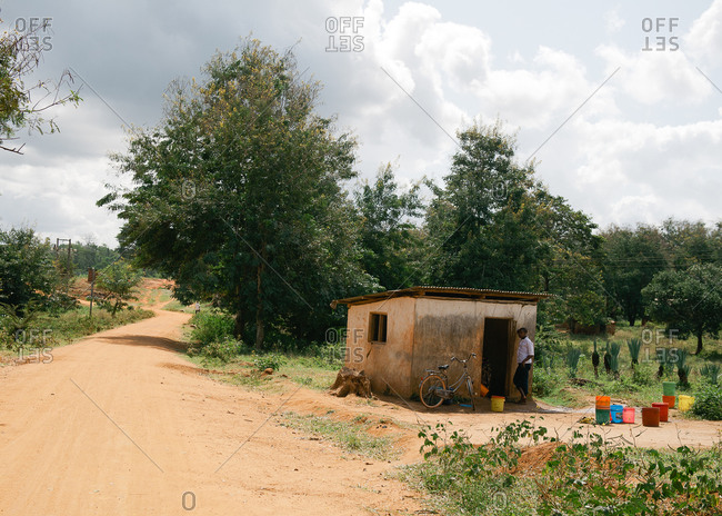 Tanzania - circa June 2012: A man stands outside of a shack on a dirt road