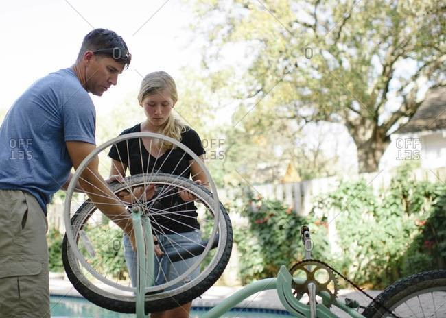 Dad helping daughter fix bike tire