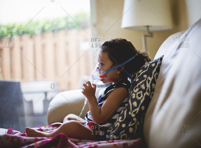A girl with asthma sits on her couch breathing into a nebulizer