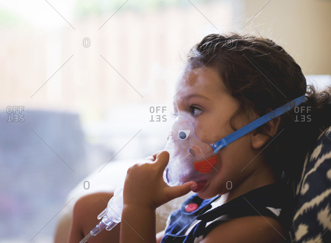 A girl with asthma breathes into a nebulizer
