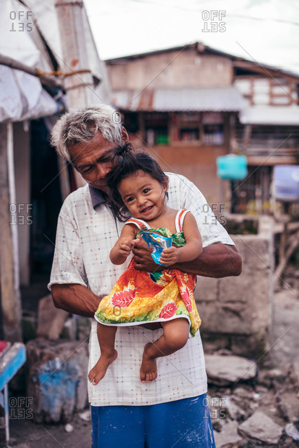 Philippines - March 24, 2015: A grandfather holds his granddaughter in a Southeast Asian village