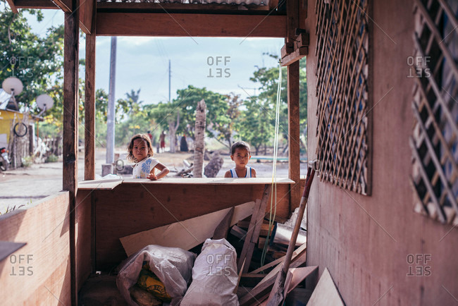 Philippines - March 24, 2015: A young girl and boy look into a patio in the Philippines