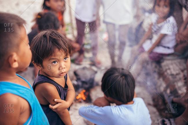 Philippines - March 24, 2015: Filipino children gather around a fire
