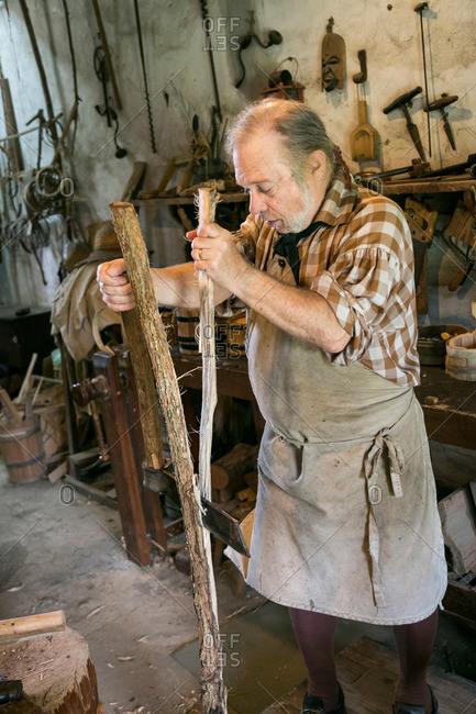 Mt. Pleasant, South Carolina - August 28, 2015: Craftsman splitting wood at Middleton Plantation in Mt. Pleasant, South Carolina