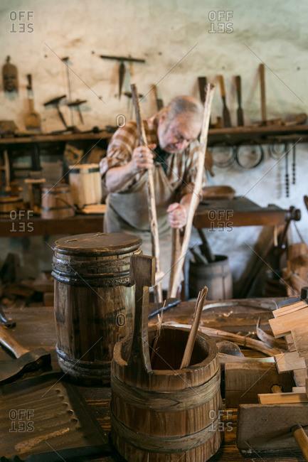 Mt. Pleasant, South Carolina - August 28, 2015: Middleton Plantation craftsman splitting wood in Mt. Pleasant, South Carolina