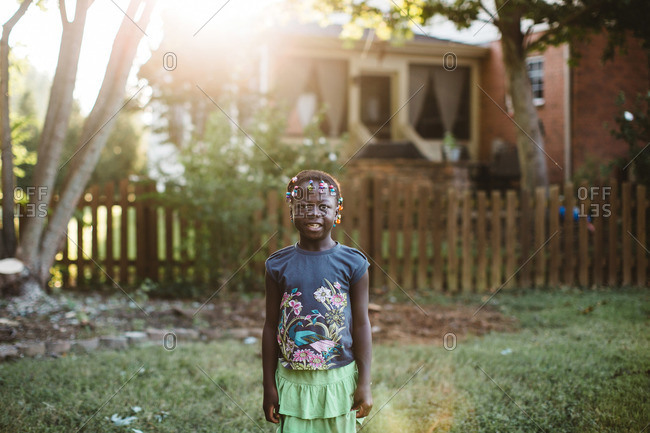 Little girl smiling while standing in sunny yard