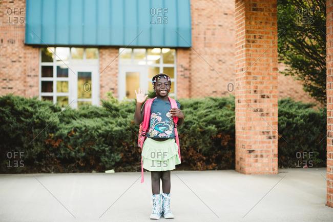 Girl waving goodbye outside of school