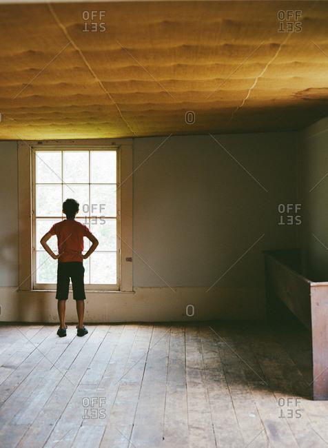Boy Standing In An Empty Rustic Room