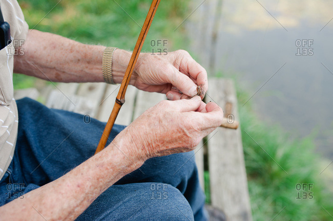 Senior man hooking a worm to fishing line