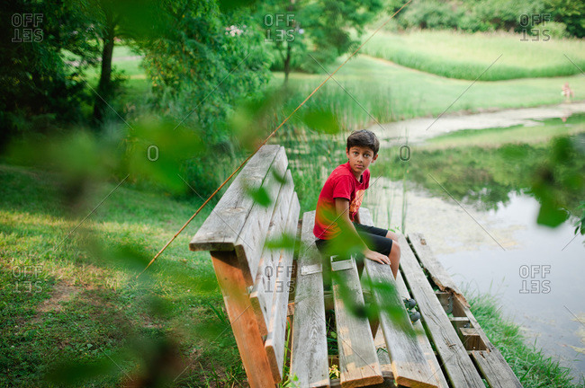 Boy sitting on a bench while fishing