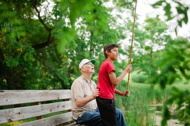 Grandfather helping his grandson fish