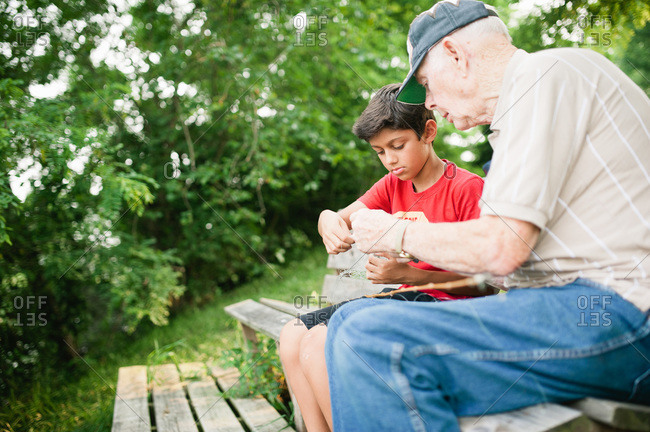 Grandfather helping his grandson put bait on fishing line