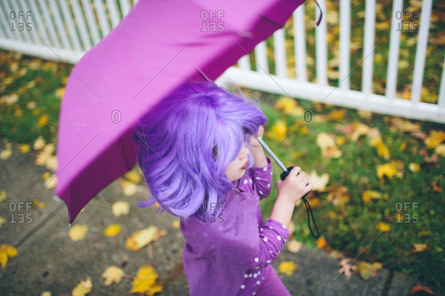 Girl in a purple wig carrying an umbrella
