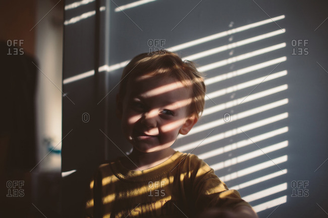 Little Boy Standing In Shadows Cast By Window Blinds Stock Photo