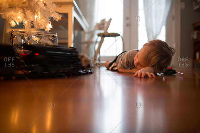 Little boy lying on a floor watching a toy train