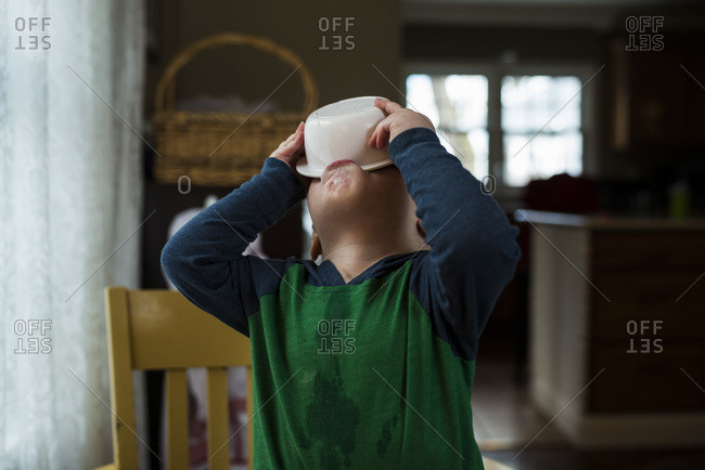 Boy drinking milk from his cereal bowl