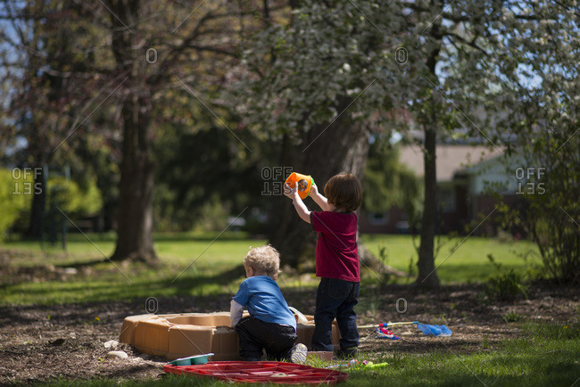 Two toddlers play in a sandbox in the spring