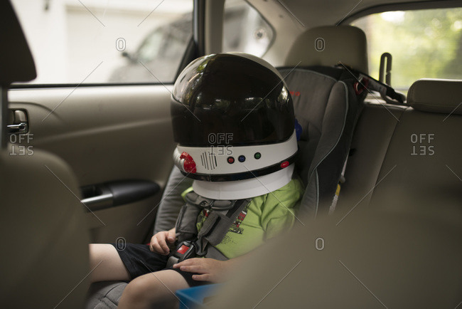 Child in backseat of car with spaceman astronaut helmet