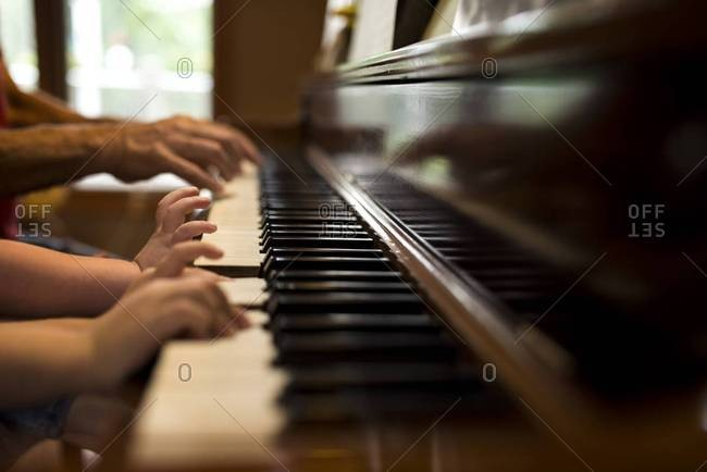 Hands of child and grandfather playing the piano