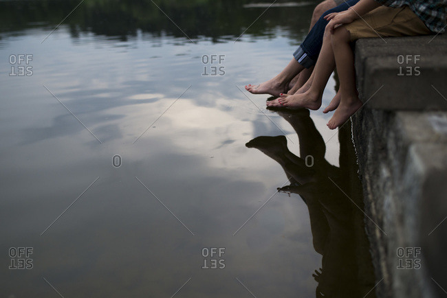 Family dangles their bare feet in the lake water