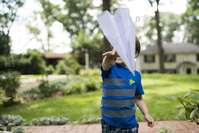 Child throwing paper airplane outdoors