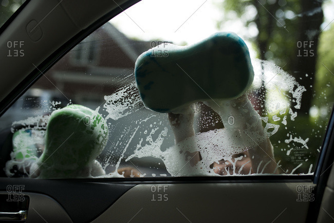 Two boys wash car window with soapy sponges