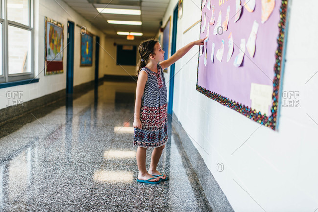 Girl pointing to a board at her school