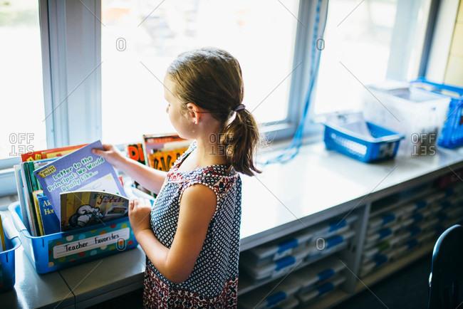 Girl selecting a book in a classroom
