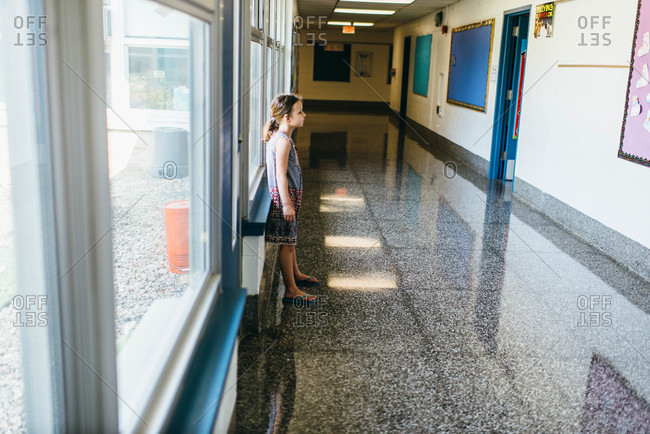 Young girl standing in a school hallway