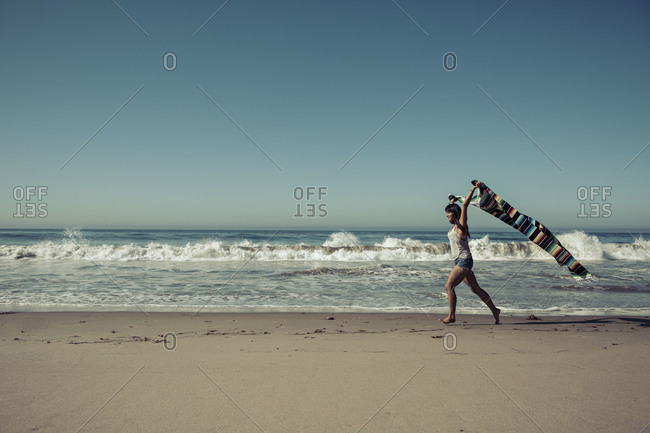 Woman running with a multi-colored blanket on a beach