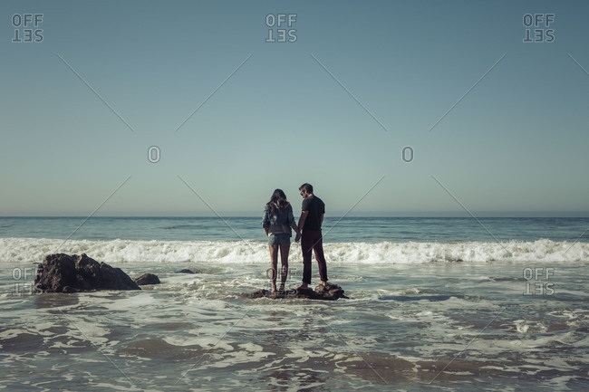 Young couple standing on a rock on the beach holding hands