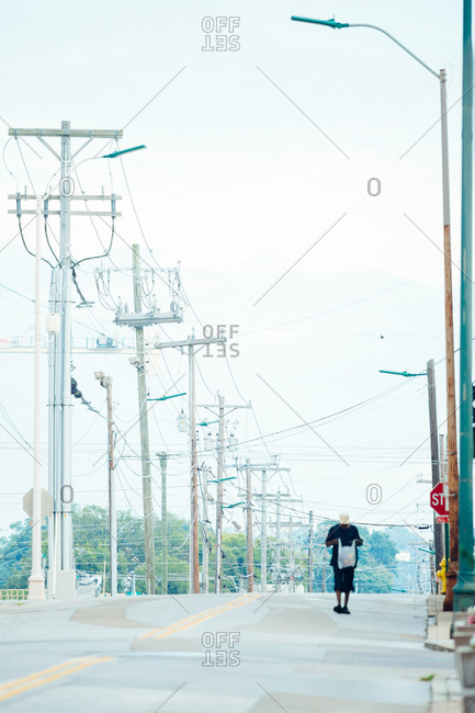 Person walking on road with power lines overhead