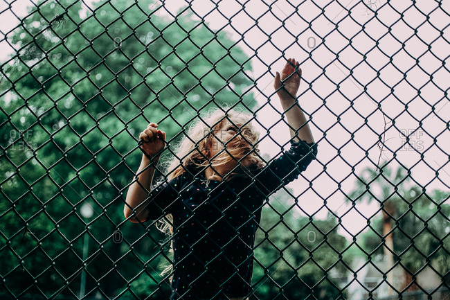 Girl climbing on a chain-linked fence