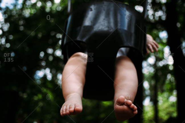 Feet of a baby boy in a bucket swing