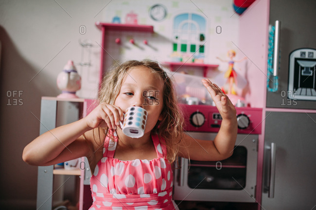 Little girl pretending to drink from a miniature coffee cup