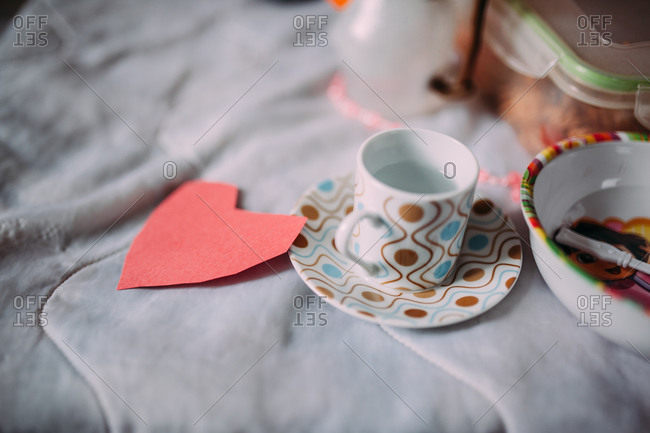 Miniature coffee cup and a paper heart