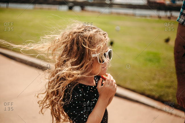 Little girl in sunglasses with windblown hair