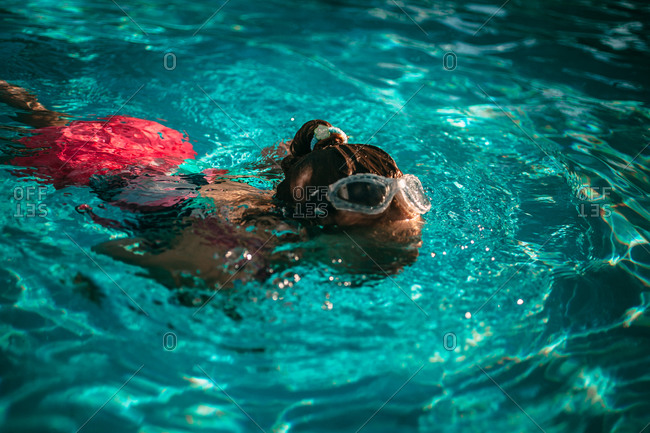 Little girl swimming in a pool with goggles on her head
