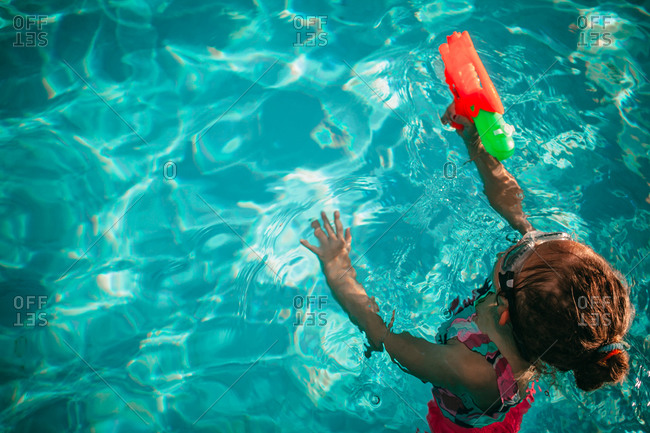 Little girl in a swimming pool with a squirt gun