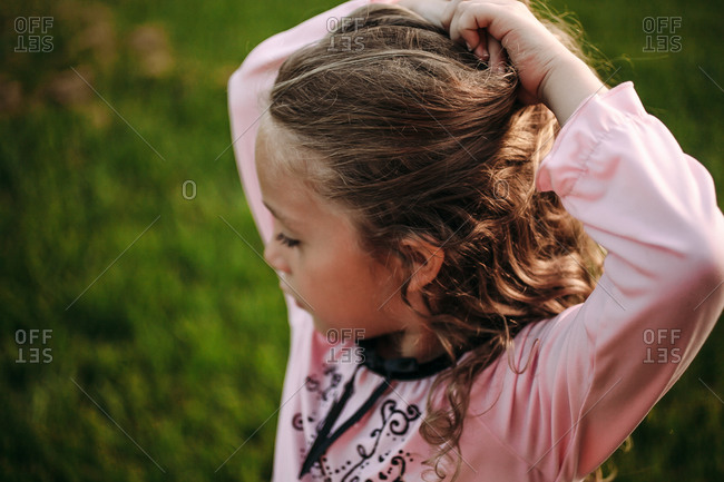Little girl pulling up her hair