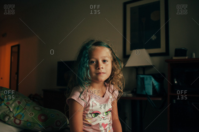 Little girl with blue hair sitting on the edge of a bed