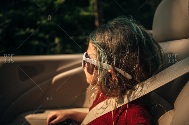 Little girl in a convertible wearing sunglasses