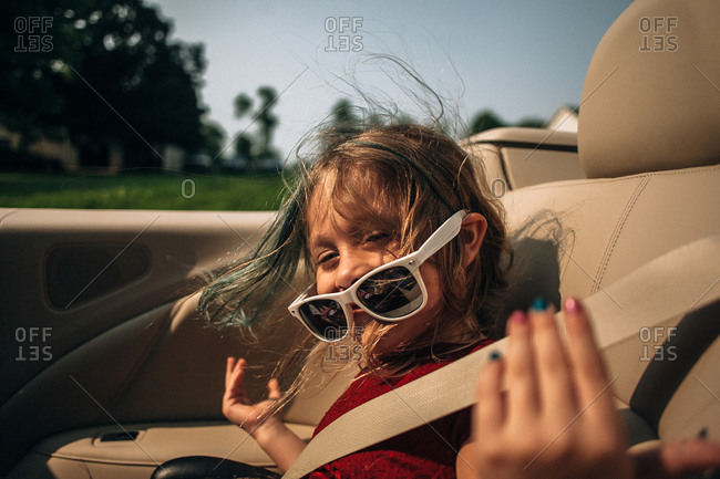 Little girl posing in the back seat of a convertible