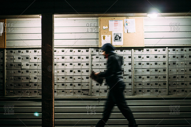Man walking in front of mailboxes