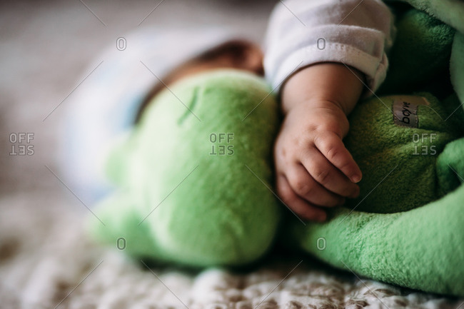 Sleeping baby boy's arm wrapped around a stuffed frog
