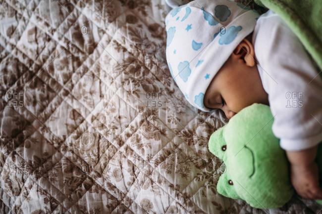 Baby boy sleeping with a stuffed frog